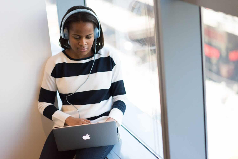 woman transcribing audio on laptop